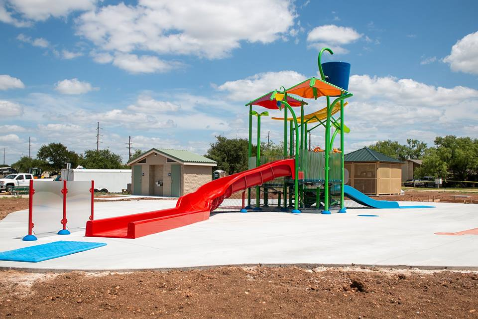 Colorful splash pad with multiple slides and a large bucket at the top for dumping water 1