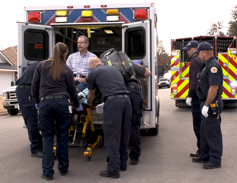 EMS and Firefighters assisting a heart attack victim onto an ambulance