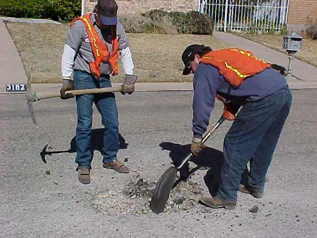 Two Workers Performing Asphalt Maintenance