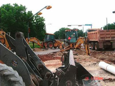Multiple backhoes and trucks at water line construction site